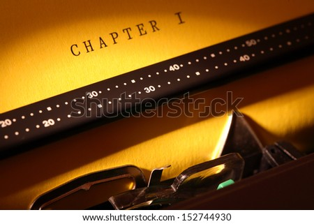 Closeup of electrical typewriter with yellow paper sheet. Inscription Chapter One on paper - stock photo