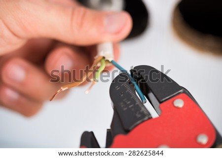 Closeup Of Electrician Hands Stripping Electrical Wires For Wall Socket - stock photo