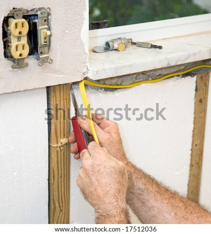 Closeup of electrician's hands as he installs electric wiring in styrofoam insulation.  Authentic and accurate content depiction in accordance with industry code and safety regulations. - stock photo