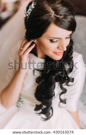 Closeup of elegant sensual brunette bride in beautiful white dress posing indoor sitting on bed - stock photo