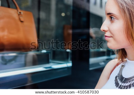 Closeup of elegant woman looking at boutique showcase - stock photo
