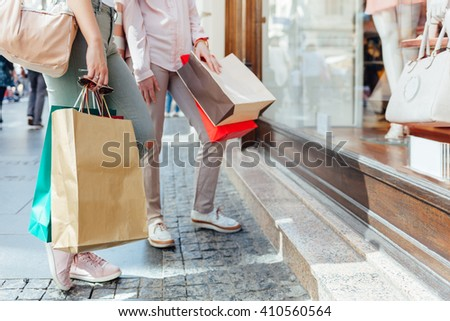 Closeup of elegant women with shopping bags looking at boutique showcase with copy space - stock photo