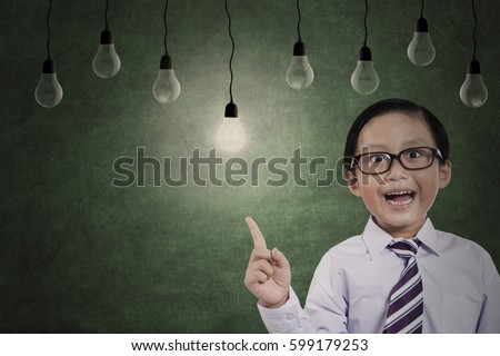 Closeup of elementary student is getting an inspiration and standing in the class with light bulbs