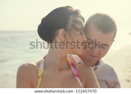 Closeup of emotional couple  on the beach. Woman kissing her boyfriend - stock photo