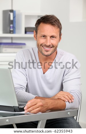 Closeup of employee in the office working on laptop computer - stock photo