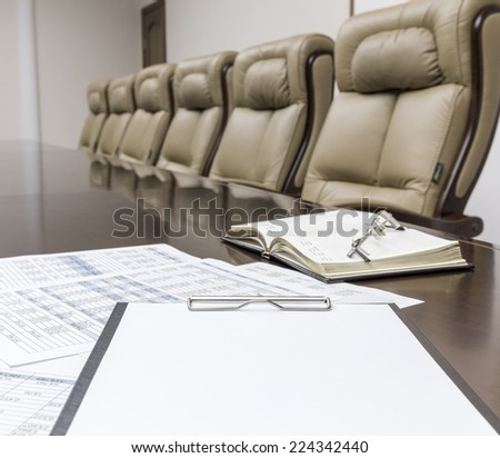 Closeup of empty clipboard on table in empty corporate conference room before business meeting in office - stock photo