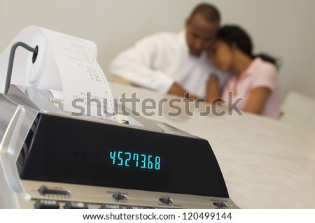 Closeup of expense receipt machine with tensed African American couple in the background - stock photo