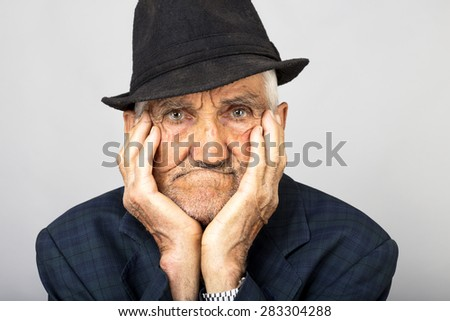 Closeup of expressive old man holding face in hands over gray background - stock photo