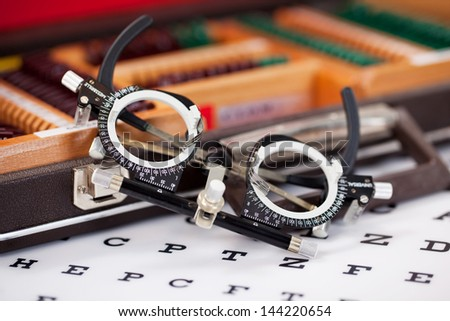 Closeup of eye examination glasses on Snellen chart - stock photo