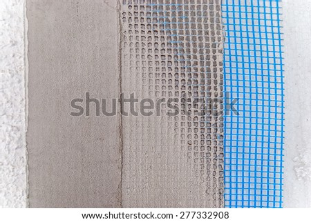 Closeup of facade layers over styrofoam insulation, mesh, plaster, cement, mortar - Shallow focus