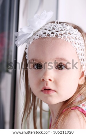Closeup of face of cute little blond girl with white headband - stock photo
