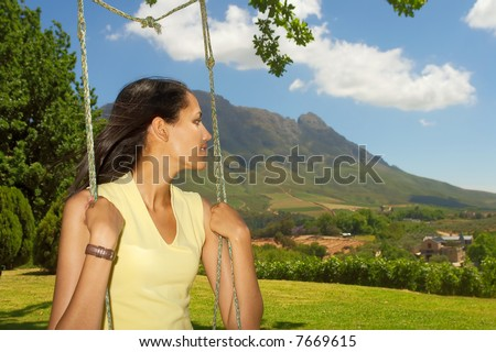Closeup of face of tender girl (mulatto/colored) sitting on swing and looking aside - awesome mountains is a background. Shot near Stellenbosch, Western Cape, South Africa. - stock photo
