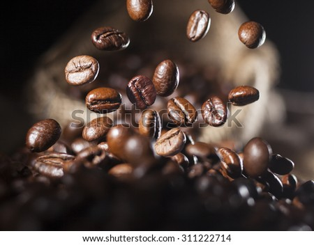 Closeup of falling coffee beans with focus on one - stock photo