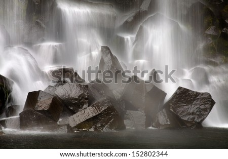 Closeup of falling water (long exposure). Svartifoss (Black waterfall), one of the famous waterfall in Iceland. - stock photo