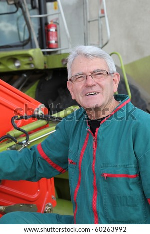 Closeup of farmer standing by harvester - stock photo