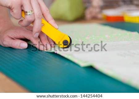 Closeup of fashion designer's hands marking on cloth in workshop