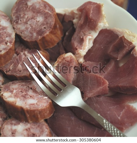 Closeup of fat salami and red meat laid on a plate, silver fork across it, concept of overeating - stock photo