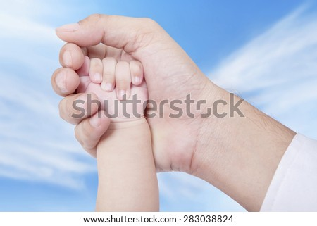 Closeup of father hand holds his baby hand on the palm, shot under blue sky - stock photo