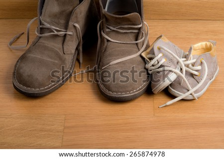 Closeup of father's shoes close to child's shoes on a parquet floor - stock photo