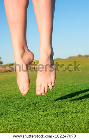 closeup of feet of jumping on green field woman - stock photo