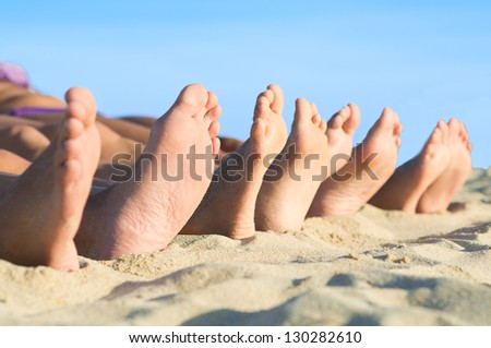 Closeup of feet row lying in line at summer beach - stock photo