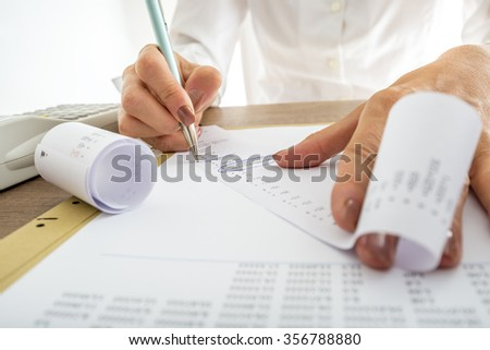 Closeup of female accountant looking through the receipts while working on a report. - stock photo