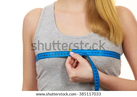 Closeup of female body. Fitness woman fit girl with measure tape measuring her chest breasts isolated on white