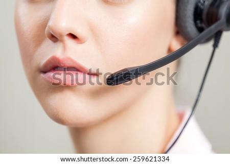 Closeup of female customer service representative wearing headset in office - stock photo