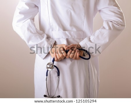 Closeup of female doctor's hand holding stethoscope