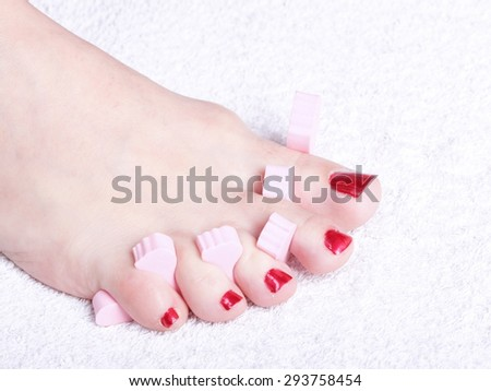 Closeup of female feet with red polished nails - stock photo