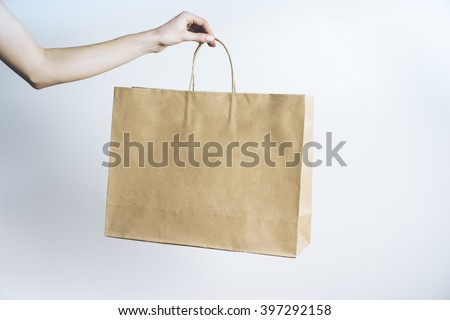 Closeup of female hand holding blank paper craft package, mock-up of template brown shopping bag with handles - stock photo