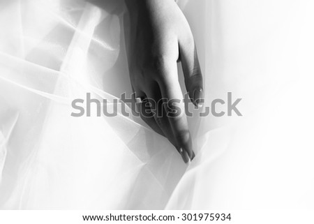 Closeup of female hand with beautiful wedding ring from precious metal on haze fabric of bridal dress black and white, horizontal picture - stock photo
