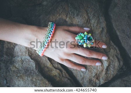 closeup of female hand with colorful  ring and bracelet on stone - stock photo