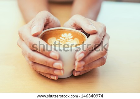 Closeup of female hands holding coffee - stock photo