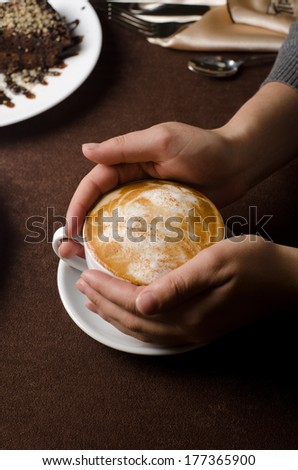 Closeup of female hands holding cup of Cappuccino
