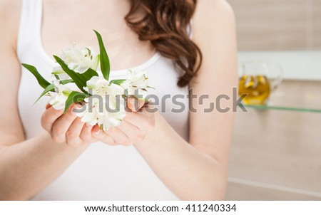 Closeup of female hands holding fresh flowers in a bathroom; beauty and skincare concept - stock photo