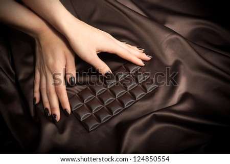 Closeup of female hands touching the dark chocolate bar - stock photo