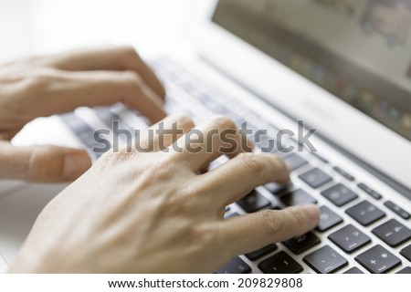 closeup of female hands typing on laptop keyboard - focus on a right hand - focus on the index knuckle