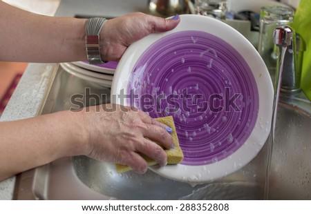 Closeup of female hands washing dish ware by spounge, indoor horizontal shot - stock photo