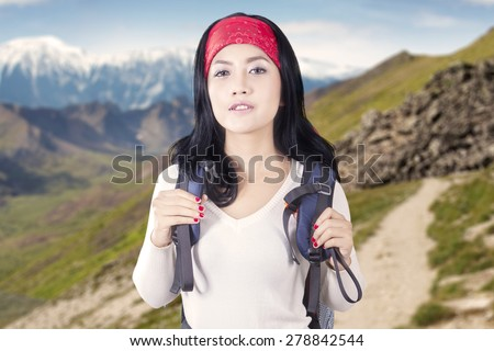 Closeup of female hiker carrying backpack while standing on the mountain edge