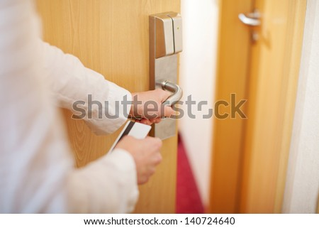 Closeup of female housekeeper's hands holding cardkey and opening door of hotel room - stock photo