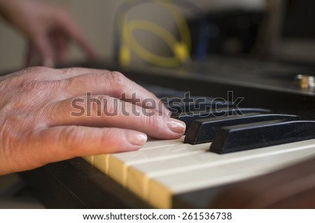 Closeup of female musician hand playing synthesizer