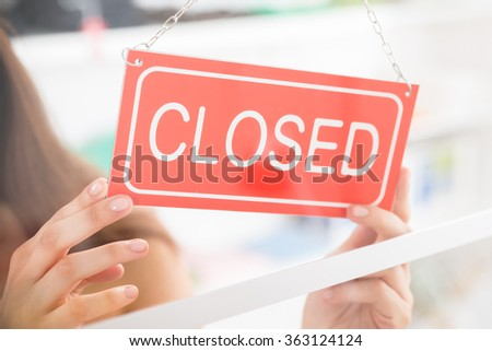 Closeup of female owner holding closed sign in clothing store - stock photo