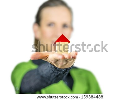 Closeup of female real estate agent holding wooden toy house in her palm. Over white background.