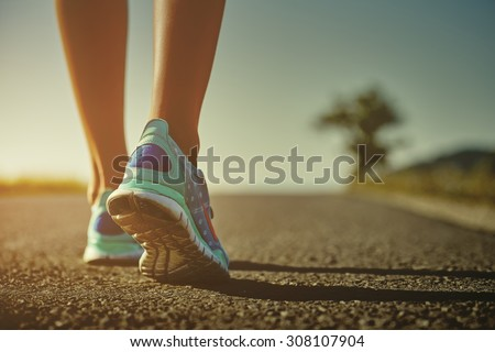 Closeup of female runner shaved feet in running shoes going for a run on the road at sunrise or sunset. Shallow depth of field, toned with instagram like filter, flare effect. - stock photo