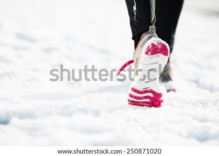 Closeup of female runner shoe running on snow - stock photo