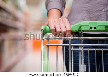 Closeup of female shopper with trolley at supermarket - stock photo
