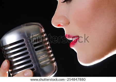 Closeup of female singer holding a classic elvis-microphone close to her red lips