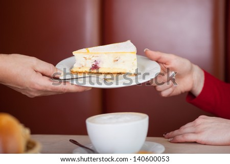 Closeup of female worker's hand giving pastry to customer in coffee shop