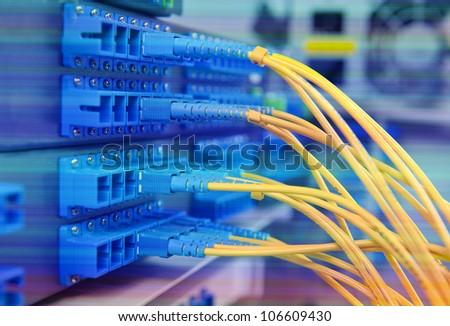 closeup of fiber optical network hub and cables - stock photo
